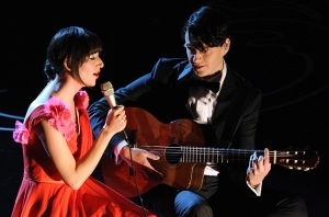 Karen O (left) and Ezra Koenig (right) sit on the Oscar stage steps to sing